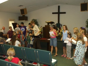 Volunteers leading children in singing