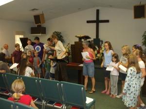 Volunteers leading children in singing